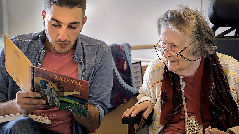 A man reads Kalevala out loud, an elderly woman listens.