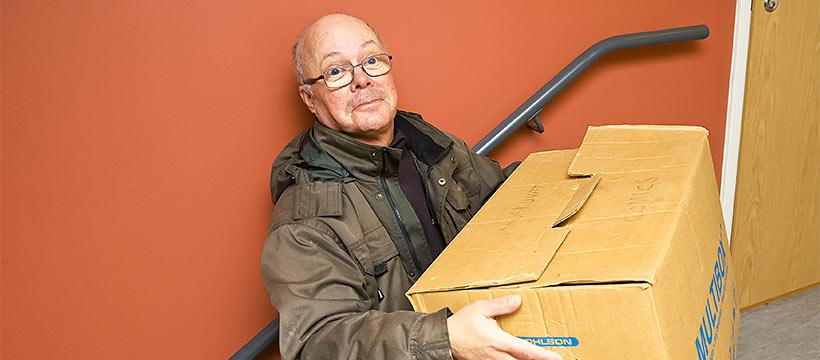 Mies kantaa muuttolaatikkoa.
