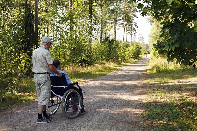 avustaja työntää henkilöä pyörätuolissa metsätiellä