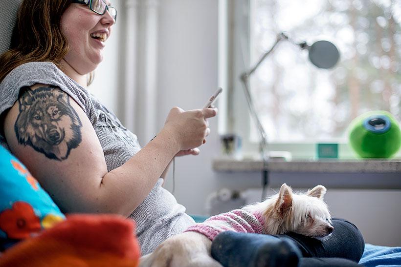 Nuori nainen istuu sängyllä koiran kanssa.