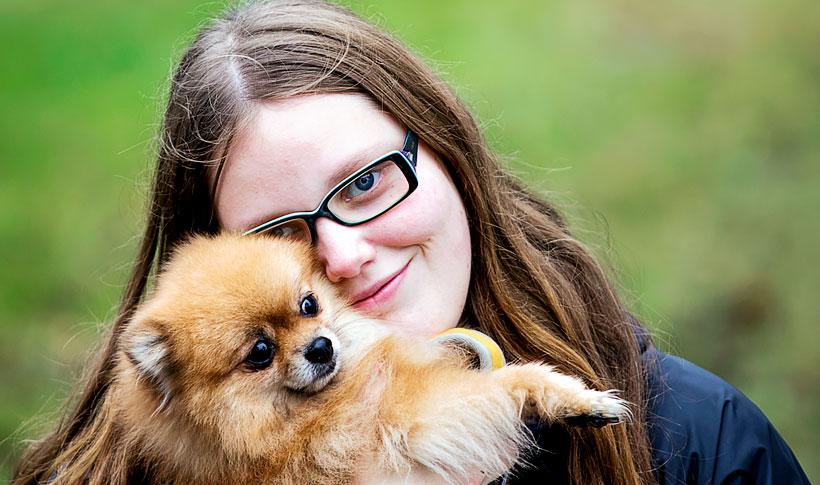 Nuori nainen, jolla on pieni koira sylissään.