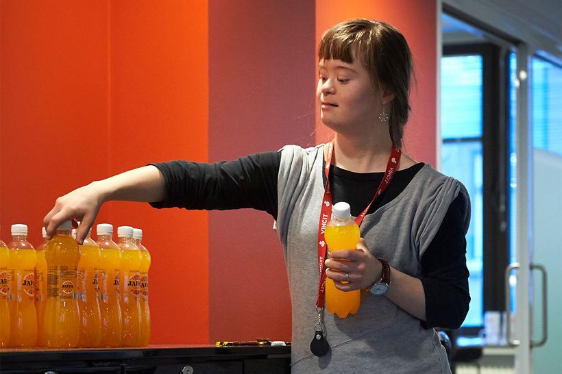 Nuori nainen asettelee limonadipulloja pöydälle.