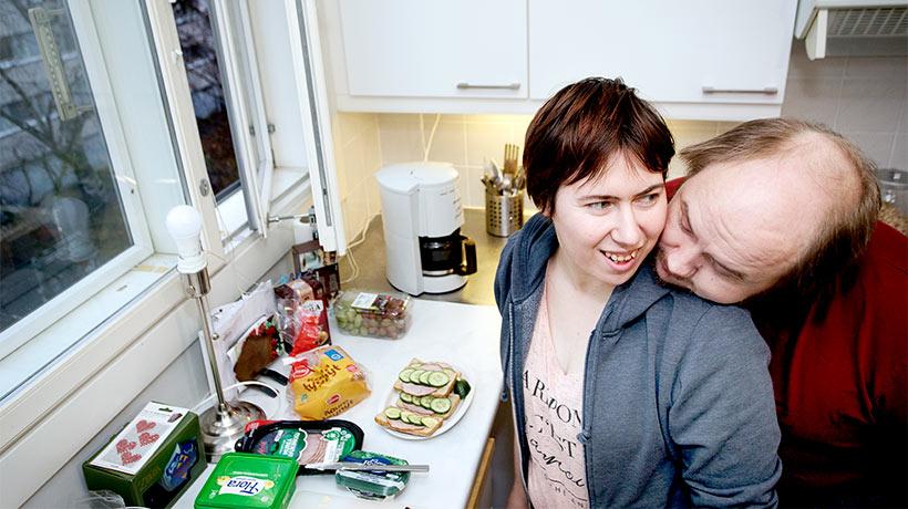 pariskunta kotonaan keittiössä