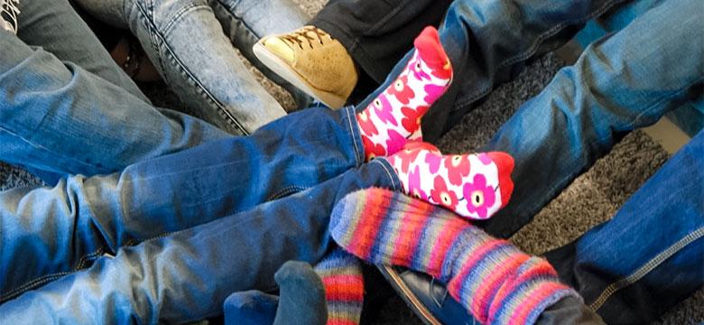 Lähikuva jaloista, joissa on erivärisiä sukkia.