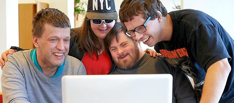 Ryhmä iloisia ihmisiä tietokoneen äärellä.