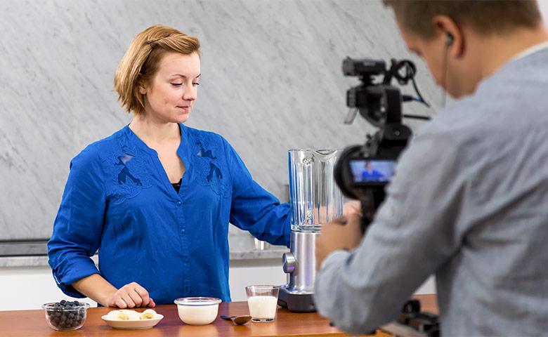 Nainen valmistaa juomaa. Mies kuvaa videota.
