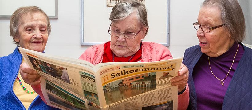 Kolme naista lukee Selkosanomia. Kuva: Ann-Britt Pada.