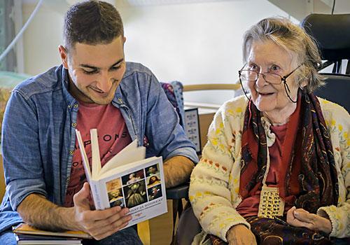Waleed Al Talib lukee ääneen Paula Elomaalle Myllypuron monipuolisessa toimintakeskuksessa Helsingissä.