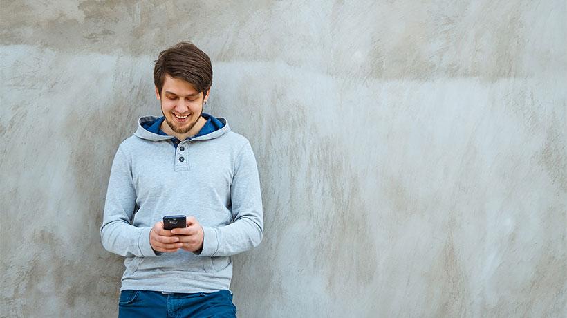 Nuori mies nojaa seinään ja käyttää matkapuhelinta.